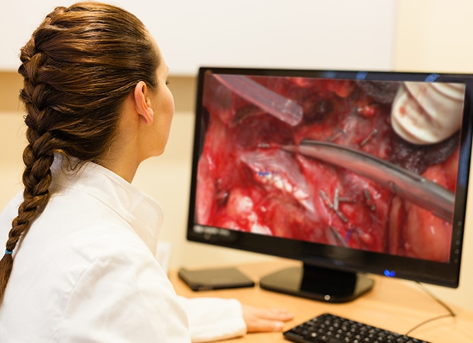 Female doctor viewing surgical footage on a desktop monitor