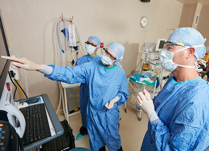 Three surgeons in active discussion in front of a display