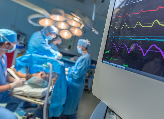 View of an OR showing surgery in progress and monitors showing vital signs