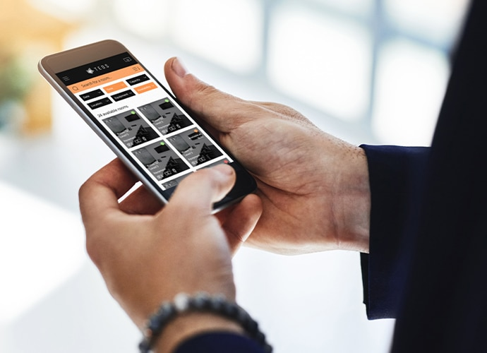 Close up image of a smartphone showing meeting room availability through TEOS application
