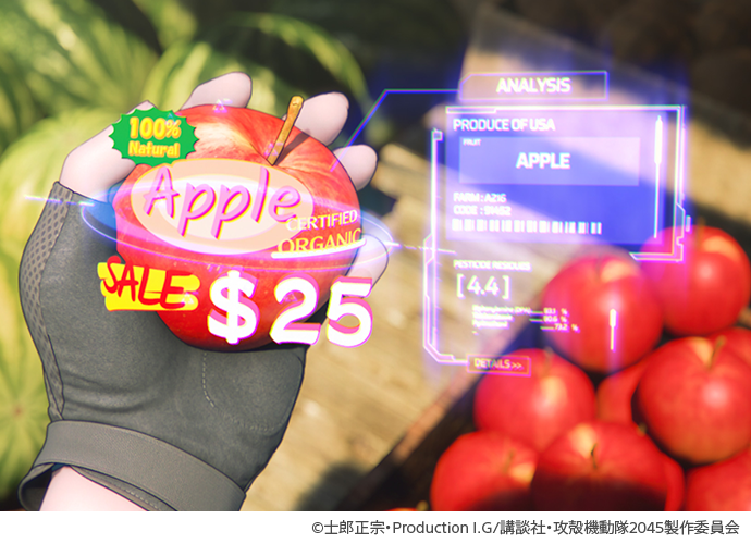 Hand holding an apple with watermelons on the floor