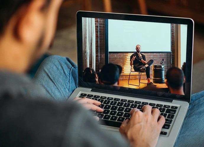 Filmmaker watching live webinar on laptop computer