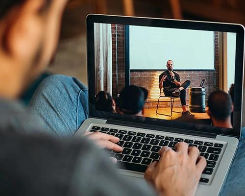 Man sitting down, typing on his laptop, watching a webinar