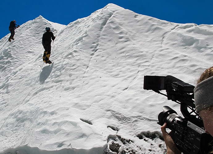 Two men skiing up a slope and being filmed by a Sony camcorder