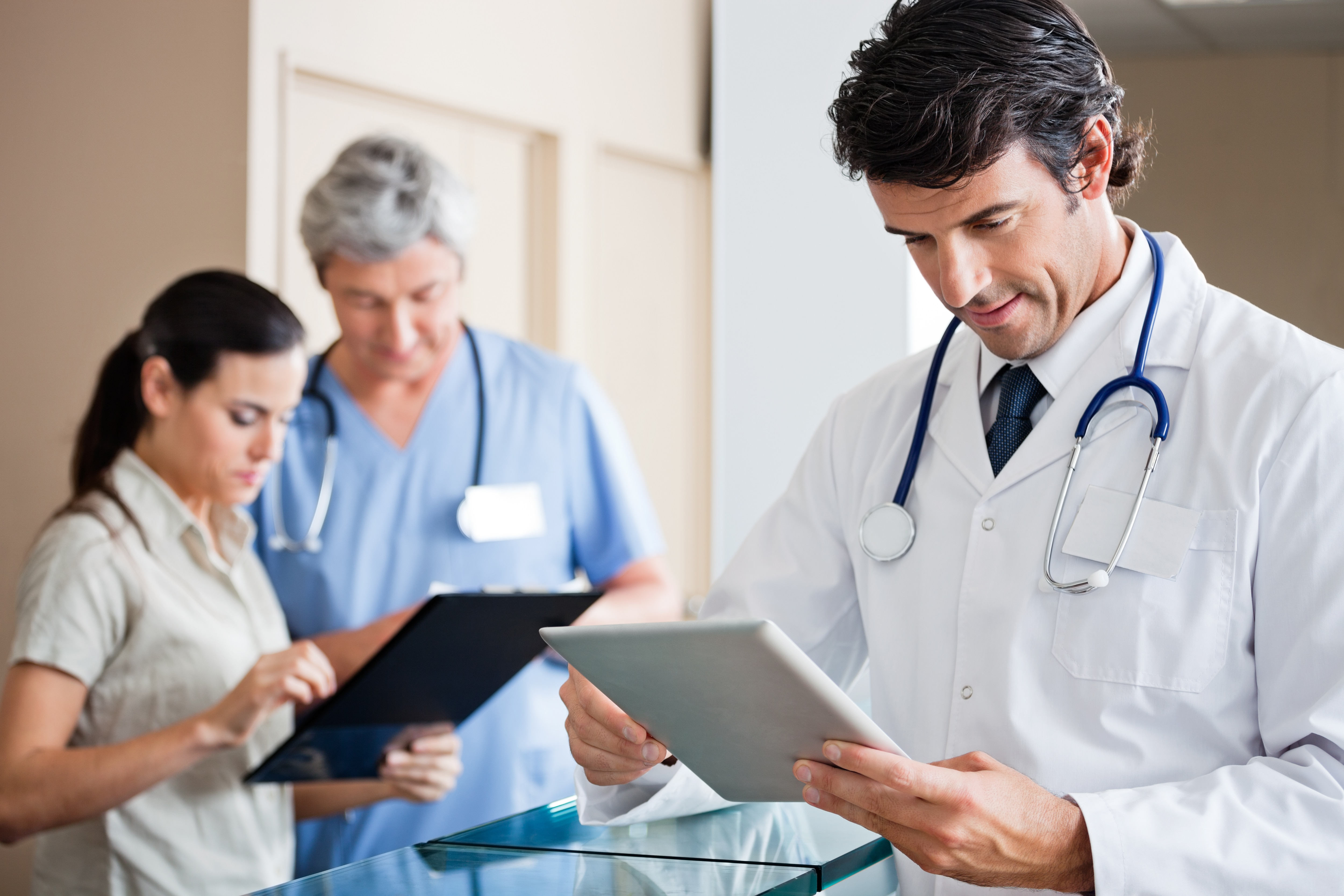Doctor and surgical staff looking at tablets