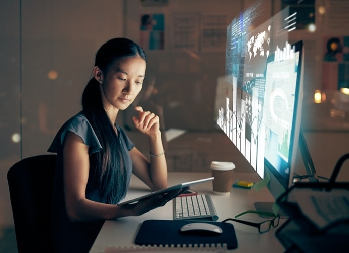 woman sitting at desk looking at pad with monitor in front of her