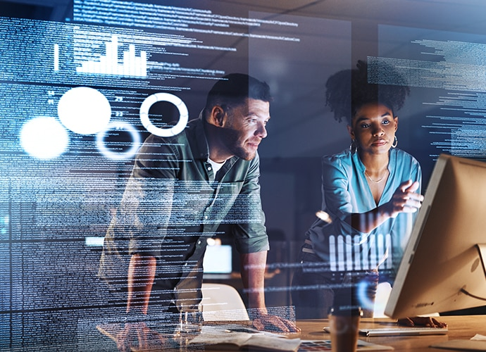 Man and woman standing in front of a transparent screen, with writing across the screen, talking and pointing at a monitor.