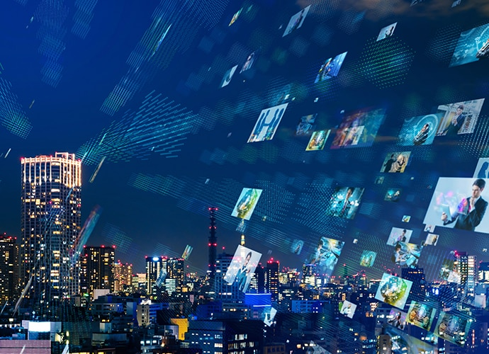 City skyline at night with digital images in the sky
