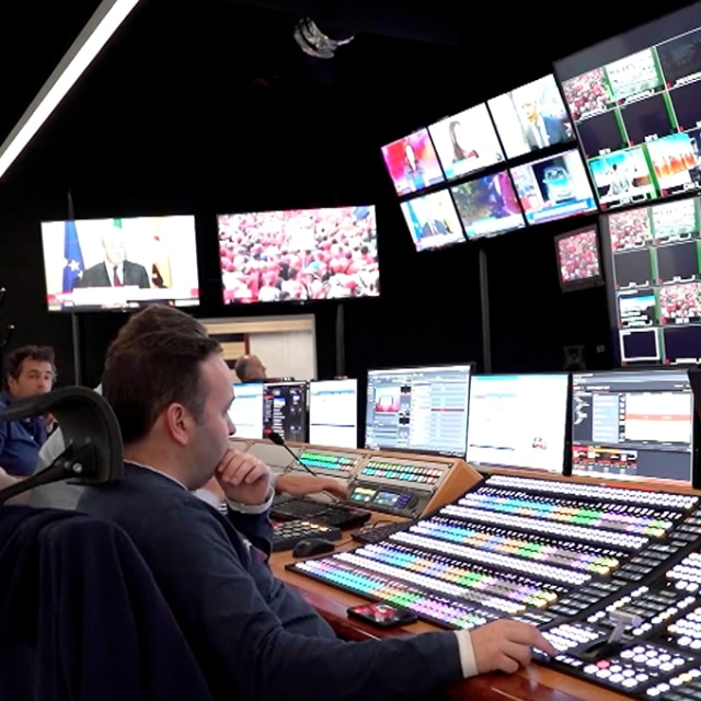 Man sitting at a production studio in front lots of monitors and switchers